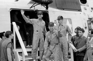 Three men in jumpsuits descending steps from a plane or helicopter.