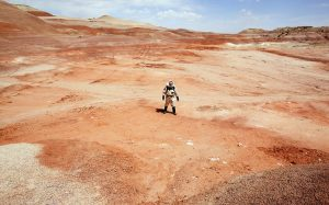 Person in spacesuit in vast expanse of barren red dirt.