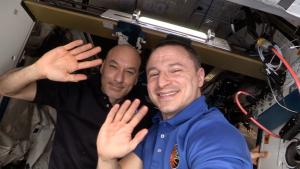 Astronauts Luca Parmitano and Drew Morgan inside ISS, waving.