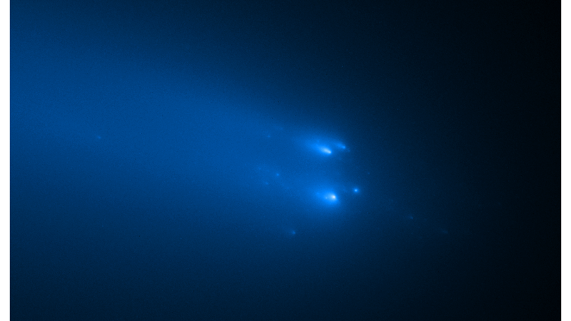 About 13 easily visible light specks on a dark blue background apparently hurtling through space with gaseous tails.