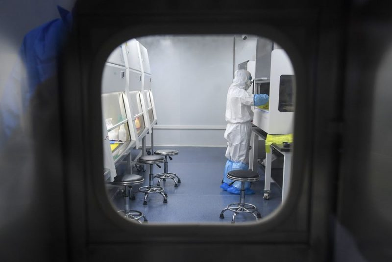 View through window in door of white-suited person working next to large white cabinets in a sealed room.