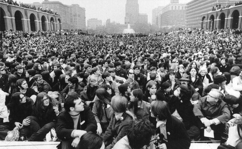 Black and white photo of gigantic crowd in 1970 garb and hair.