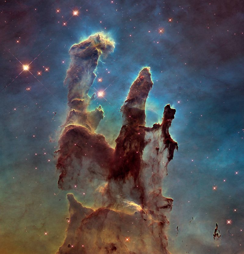 Huge mostly brown finger-like clouds reaching upward in a starry sky with bluish clouds.