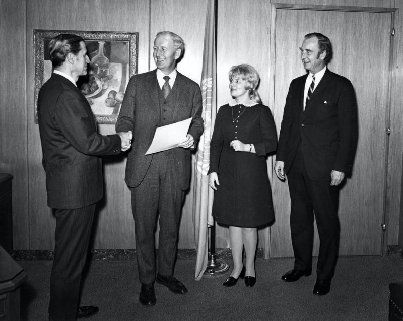 Men in suits and woman in a dress standing in a paneled room with UN flag behind them.