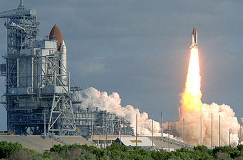 Space shuttle atop a column of flame with billows of steam below, near launch tower with another shuttle.