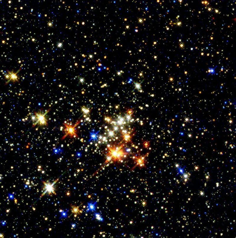 Dense field of multicolored stars with a scattered bunch of brighter ones near center.