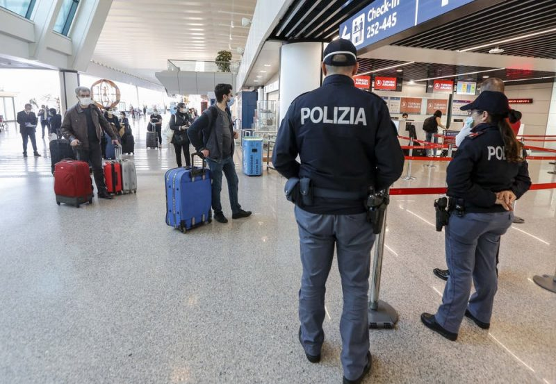 Airport concourse with travelers and two police officers.