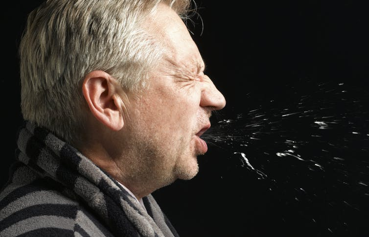 side view of an older white man sneezing with particles visible in front of him.