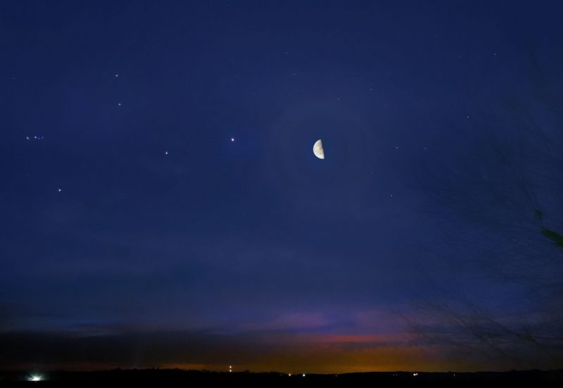Crisp crescent moon and 3 planets in a deep blue sky.