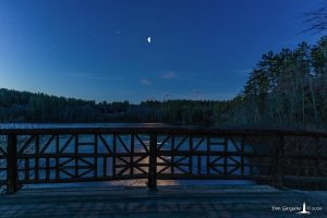 Bridge railing in foreground, moon and planets in background over a lake.