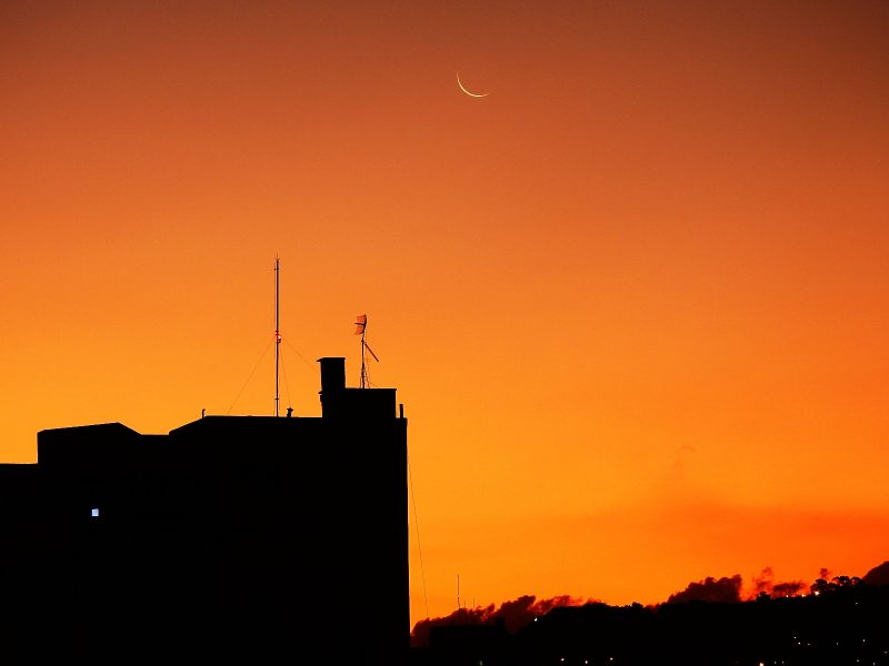 Thin crescent of young moon against an orange sky above a dark building.