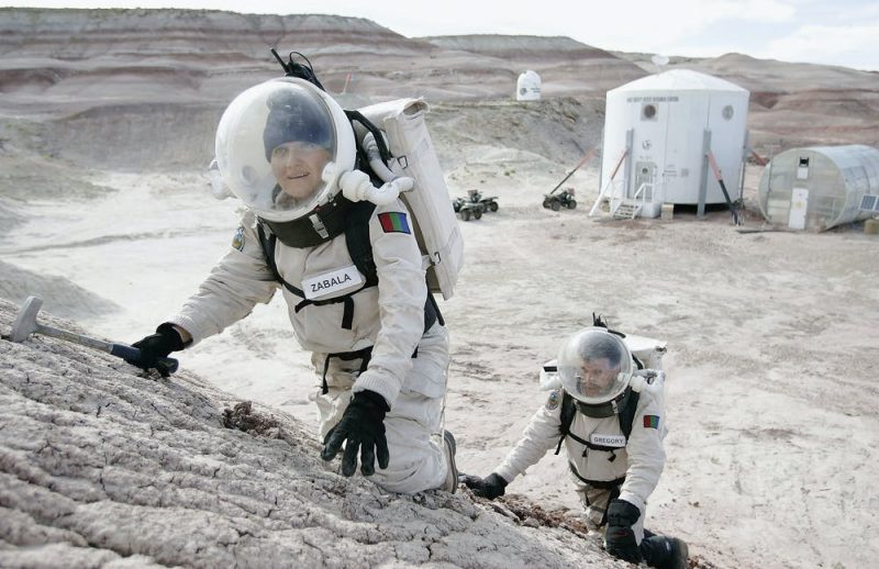 Two people in spacesuits climbing up a barren slope with white cylindrical buildings in background.