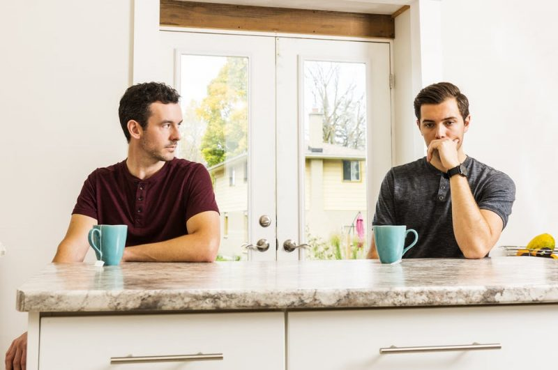 Two young men sitting at a counter with coffee cups.