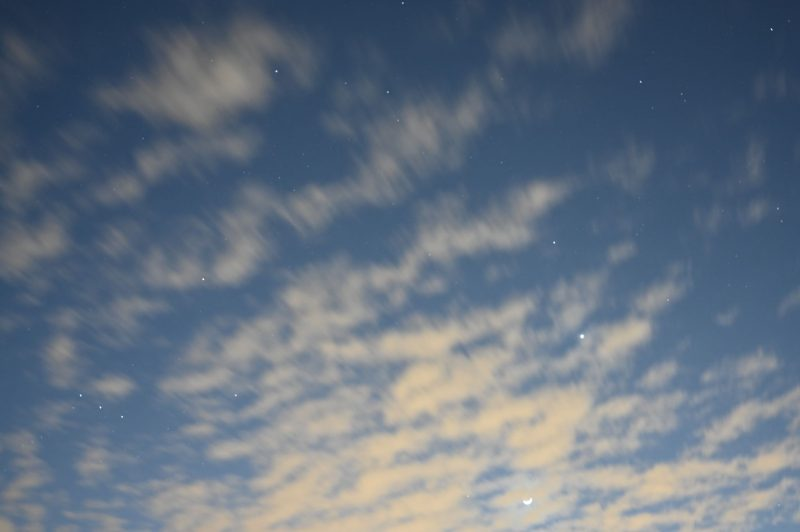 Blue daytime sky, with clouds, with stars showing up behind the clouds, and also the moon and Venus.