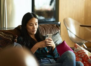 Woman sitting on a couch looking at her phone.