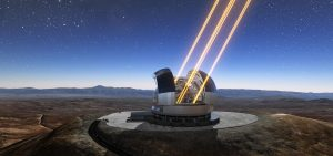 Telescope shooting lasers into dark blue sky with stars.