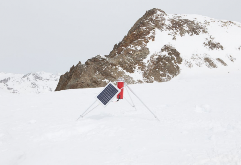 Red rectangle with solar panel on glacier with rocky mountaintop in background.
