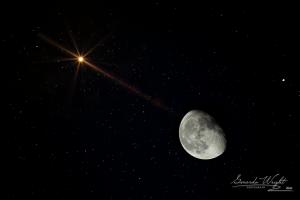 Bright reddish star close to gibbous moon.
