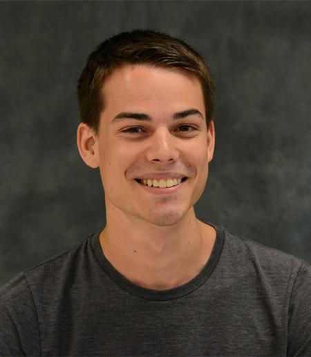 Smiling man in t-shirt on dark background.
