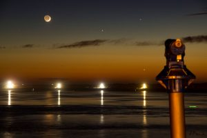 Thin crescent moon with earthshine on the rest of the face, two planets over seaside.