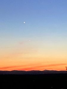 Sky fading from blue to orange at horizon with two white dots.