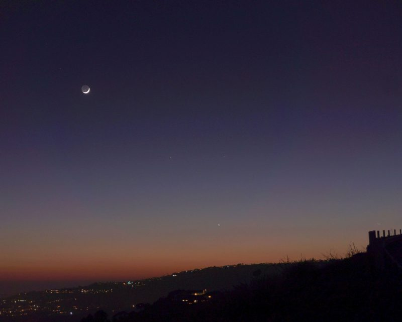 Slim crescent mood with two white dots lower in the twilit sky.
