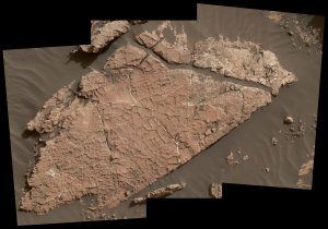 Brownish rock covered in cracks, surrounded by brownish sand.