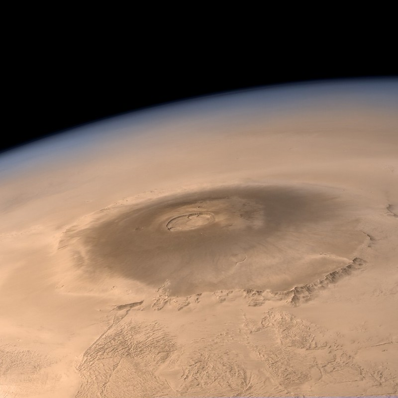 A very large volcano on red Mars, with the limb of Mars showing against black space.