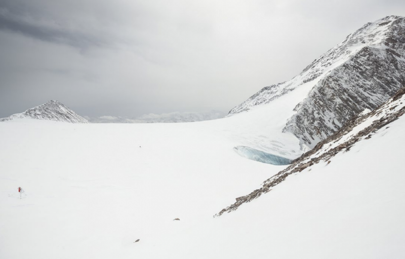 Sweeping glacier amid rocky snowy mountaintops, under a cloudy sky, with a small device visible.