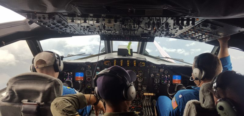 Back view of 4 people in headphones looking toward the front windows of an aircraft.