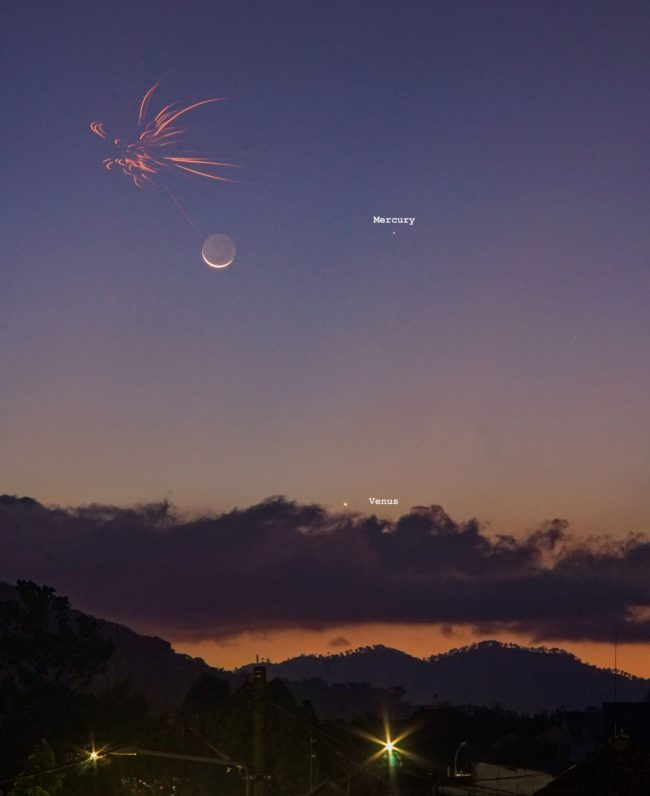 Red fireworks above slender crescent moon with Mercury and Venus as dots in twilight sky.