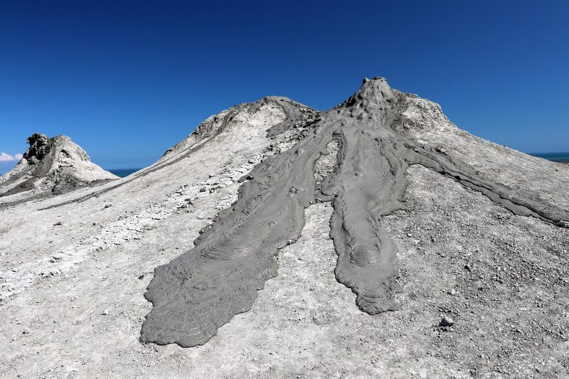 Conical gray colored hill with darker gray semi-liquid-appearing flows on it, with blue sky in background.