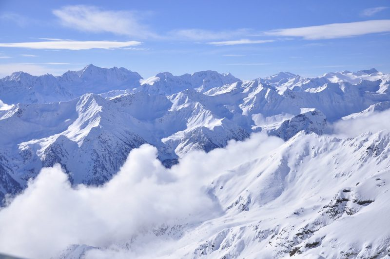 Aerial view of beautiful glistening snowy mountains with a deep foggy valley under a blue sky.