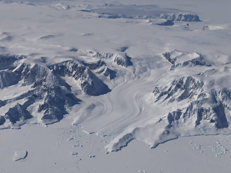 Aerial view of ice-covered mountainous landscape, glacier, ice-covered sea.