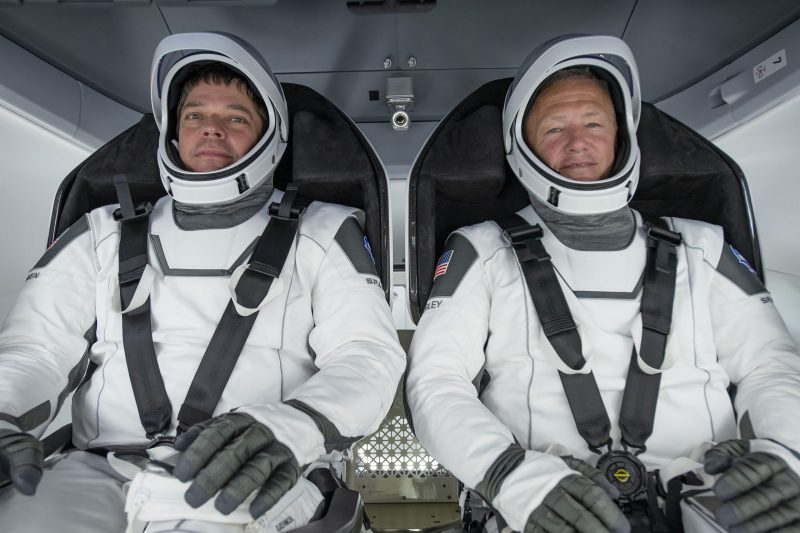 Two men in white space suits with the faceplates open, strapped into seats in a spacecraft.