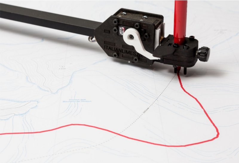 A topo map with a red line being drawn by an automatic pen on a mechanical arm.