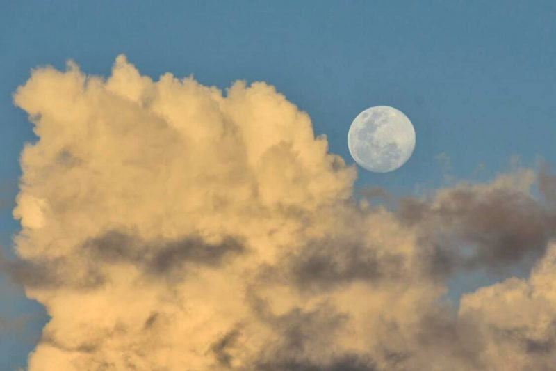 Full moon near billowing yellow clouds against a blue sky.