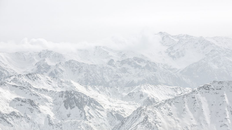 Snow-covered mountain peaks seen from above going into distant hazy horizon under white sky.
