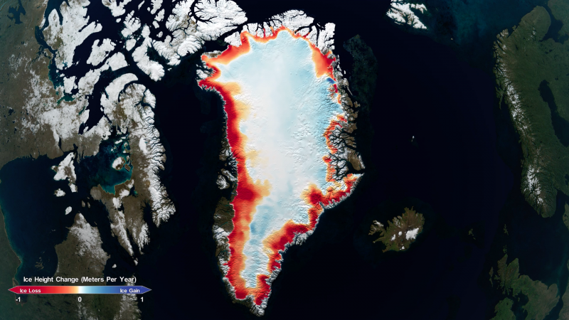 False-color satellite view of Greenland with red rim around it showing ice loss on coasts.