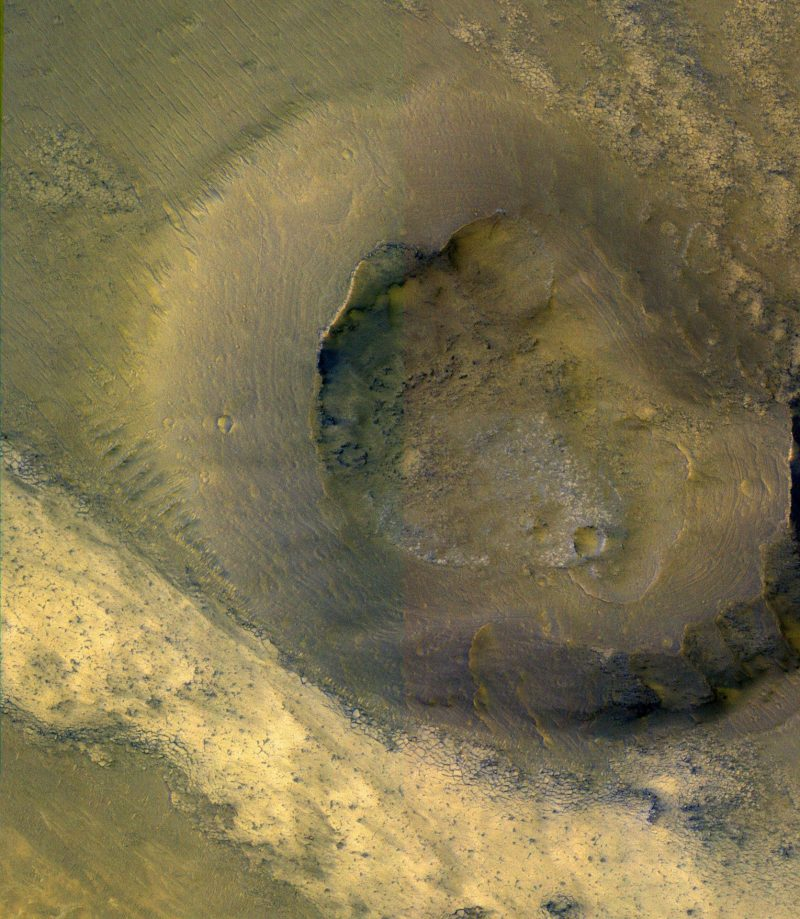 Brown and tan orbital view of a rounded hill with crater on top.