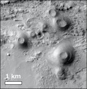 Gray conical mounds with craters on top on gray terrain.