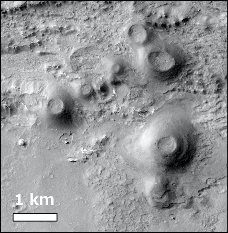 Orbital view of gray conical mounds with craters on top on gray terrain, with a line indicating one kilometer.