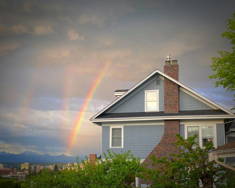 The photo shows what looks like an ordinary double rainbow with a third rainbow, at an odd angle, in their midst.