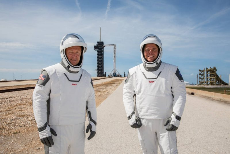 Two men in white space suits with the faceplates open, standing on a road with a rocket in the background.