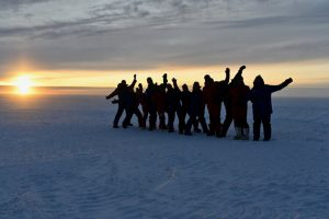 A group standing in snow, waving and posing, with the sun setting behind them.