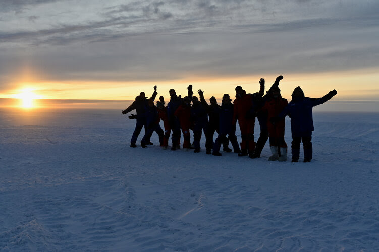 A line of about a dozen peopple standing in snow, waving and posing, silhouetted against the sun setting behind them.