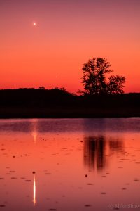 Venus and Mercury in a red twilight sky, reflecting in a lake.
