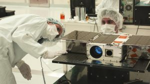 Box-like apparatus in laboratory with two technicians in lab gear.