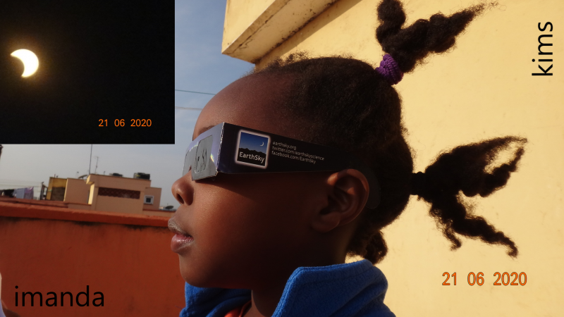 Side view of a young girl wearing EarthSky eclipse glasses