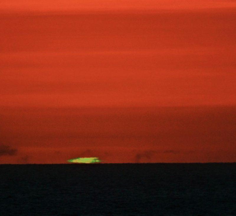 Short green streak between orange sky and dark sea.